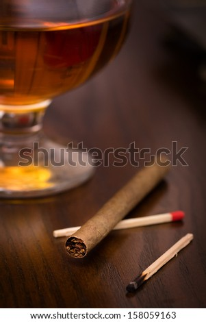 Cigarillo with glass of brandy