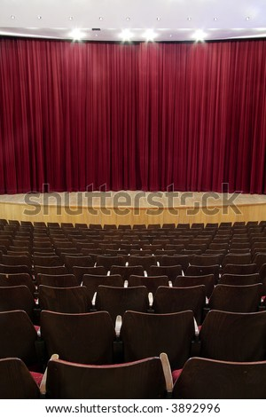 cinema, theater interior; closed red velvet curtain, wooden seats
