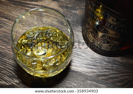 CIRCA APRIL 2015 - KWIDZYN: Glass of Chivas Regal whisky on wooden table. Chivas Regal is blended scotch whisky produced by Chivas Brothers, owned by Pernod Ricard.