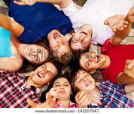 Circle of happy smiling teenage school friends lying on the grass