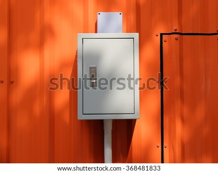 Circuit control box on orange steel wall.