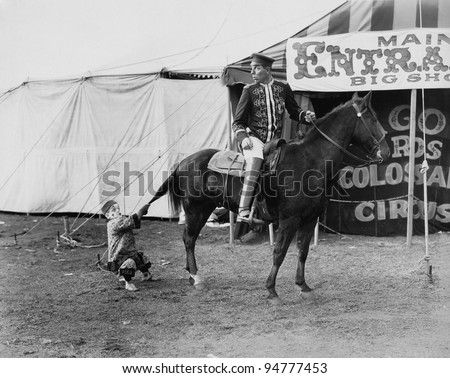 Circus performer pulling horses tail