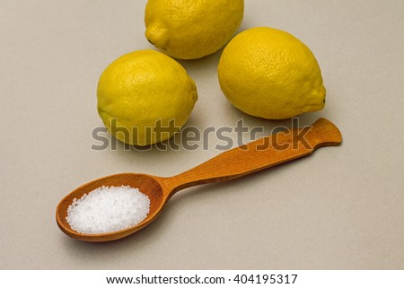 Citric acid in spoon on background of lemons. Close-up