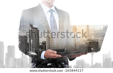 city and businessman using laptop computer. conceptual business image