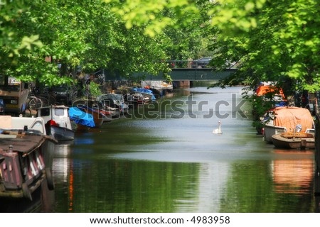 City canal (Amstel river) and boats in Amsterdam, Holland.
