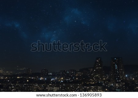 City landscape at nigh showing sky filled with stars, nebula and galaxy