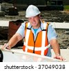 Civil Engineer Looking At The Plans To A Construction Site On The Hood Of His Car - stock photo