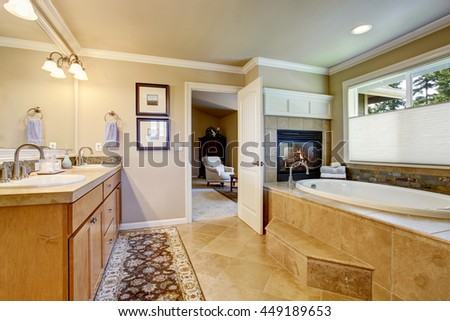 Classic American bathroom with wooden cabinets, two white sinks, tile floor, and white bath tub