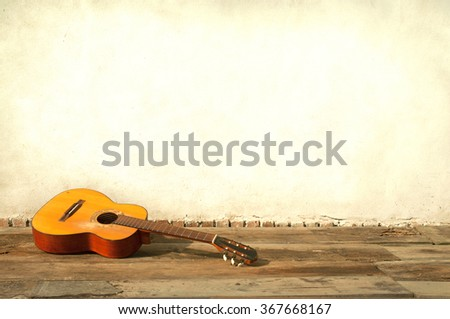 classic guitar lying in front of a wall as background