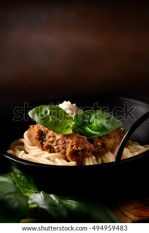 Classic Italian Spaghetti Bolognese with Parmesan cheese and basil herb garnish, set against a rustic background with copy space. The perfect image for your Italian menu cover design art.