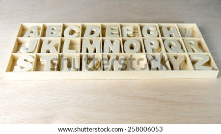 Clean and unpainted wooden alphabet letter set in boxes of compartment. Concept of back to school. Slightly defocused and close-up shot. Copy space.