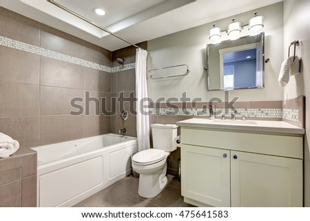 Clean bathroom interior with brown tile and white ceramic suite. Northwest, USA
