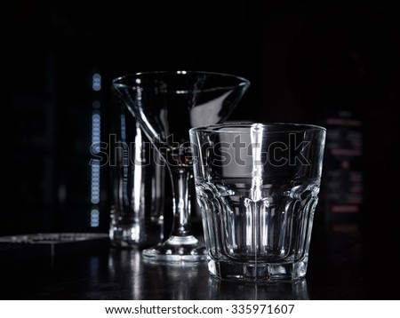 clean empty cocktail martini and old fashion rocks tumbler whiskey and collins glasses on a dark bar counter with a black background