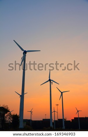 Clean energy wind turbine silhouettes at sunset, at Thailand