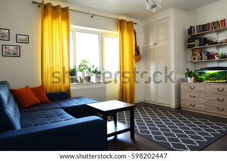 clean family room with blue couch white brick wall and yellow curtains design interior