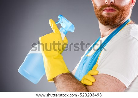 Cleaner Man Holding a Detergent Wearing an Apron and Plastic Gloves