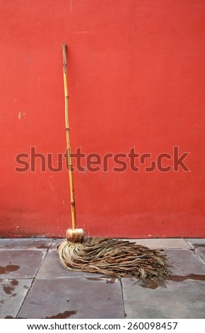 Cleaning mop lean against red wall