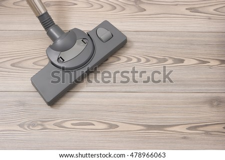 Cleans the floor of the house. Vacuuming flooring in the hallway. Brush of the vacuum cleaner on a wooden floor.
