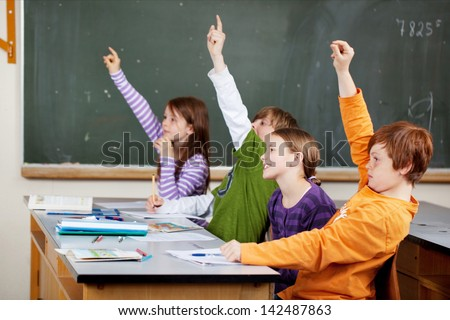 Clever young students in class holding their hands in the air in response to a question as they vie to give the answer