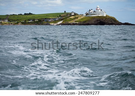 Cliff in Ireland, view from the boat. Cold Atlantic ocean, travel to Ireland with fisherman.rocks subjected to erosion, water undermines land. Seascape with sky and flying seagull.Turquoise blue water