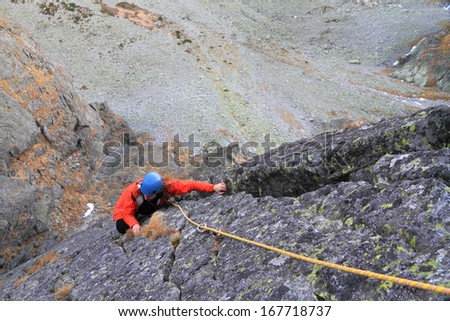 Climber following the leader on vertical granite face