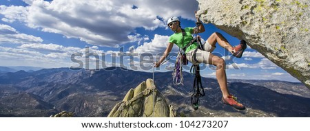 Climber rappelling from the summit of a rock spire after a challenging ascent.