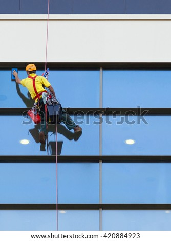 Climber worker washing windows of the modern building.
