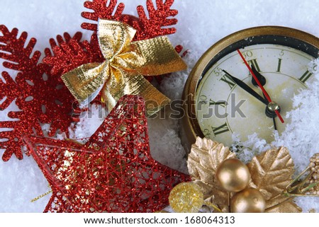 Clock and Christmas decorations under snow close up