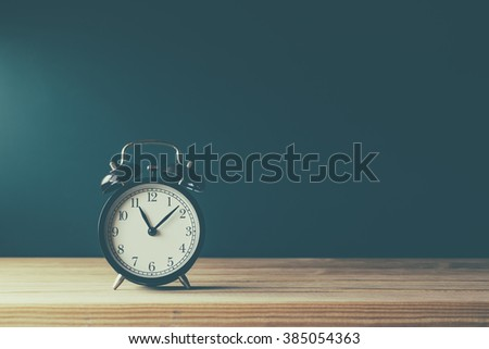 Clock on the wooden table on wooden background
