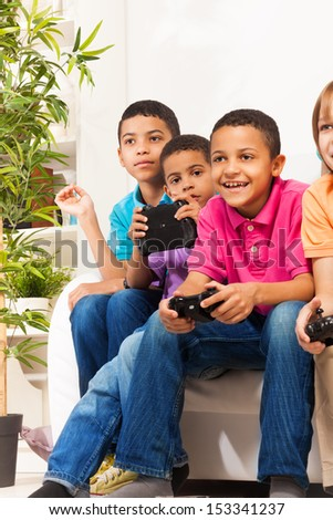 Close portrait of a group of diversity looking children boys and girls, friends, playing videogame sitting on the sofa in living room