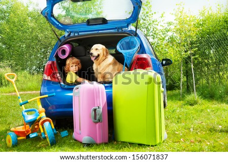 Close shoot of a car with retriever dog and three years old boy waiting in the trunk with bags for trip, trickle, ball, scoop-net