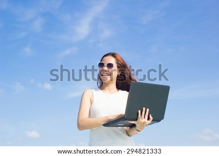 close up asian business woman working on laptop over blurred blue sky backgrounds : working woman love and happy to working.business concept.working concept.selective focus:international women's day