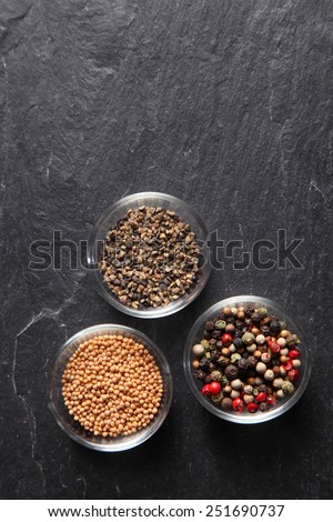 Close up Assorted Seed Type Spices on Containers Placed on slate background, Emphasizing Copy Space.