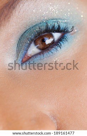 Close up beauty portrait detail of an african american black young woman attractive eye wearing colorful party blue eye make up and glitter. Cosmetics, personal care and beauty lifestyle.
