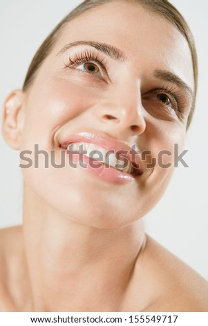 Close up beauty portrait of a young and attractive hispanic woman with bare shoulders joyfully smiling and looking up with a big fresh and happy expression, interior.
