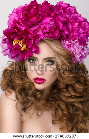 Close-up beauty portrait of young pretty girl with flower wreath in her hair wearing bright pink lipstick. Bright modern summer makeup. Beauty, spa and skincare concept