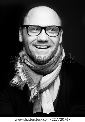 Close up black and white photo of laughing man in glasses and looking to the side.