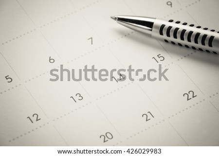 close-up calendar page and ball pen background by education business background concept.