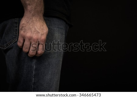 close up color image of a man wearing blue jeans and a black t shirt with his hand at his side standing in front of a black background