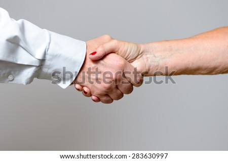 Close up Conceptual Handshake Gesture of Two Adult Hands Against Gray Wall Background.