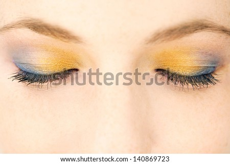 Close up detail beauty view of a young woman eyes closed wearing rainbow colorful eye shadow  make up cosmetics in blue and yellow, with healthy eye lashes.