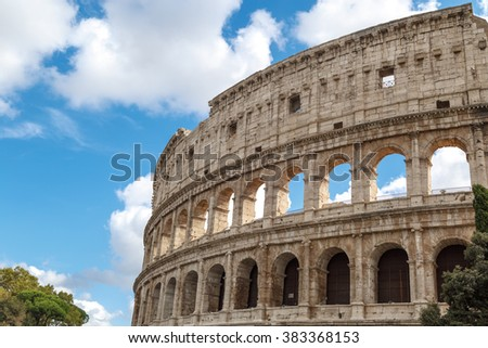 Close up detailed view of ancient amphitheatre of Colosseum built by Vespasian and Titus in Rome, on cloudy blue sky background.