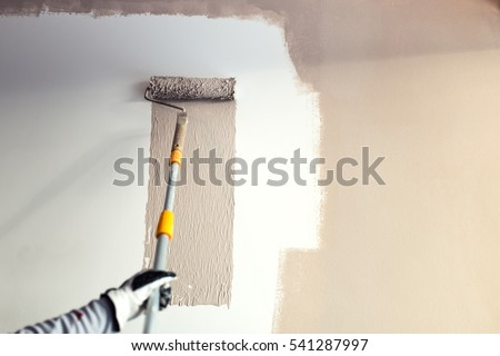 close up details of painting walls, industrial worker using roller and other tools for painting walls