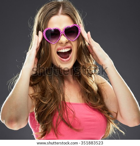 Close up face portrait of emotional woman open mouthed wearing heart sunglasses. Studio portrait of female model.