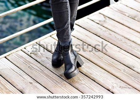 Close up fashion image of retro brutal boots, woman posing at wooden floor near sea, street style, total black, hipster look.