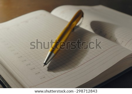 Close-up golden tip pen lying on empty pages of open notebook with a hard cover. This Office is illuminated pleasant warm light of an incandescent lamp.