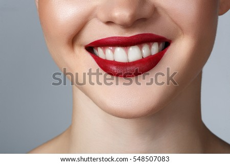 Close-up happy female smile with healthy white teeth, dark red matt lips make-up. Cosmetology, dentistry and beauty care.