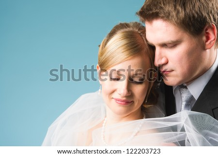 Close up happy wedding couple, both looks down, blue background
