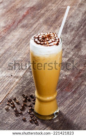 Close up iced coffee in tall glass on old wooden table
