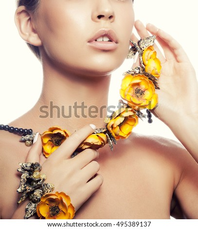 Close-up lips and shoulders of attractive caucasian young girl with natural make-up and yellow flowers necklace looking at camera. Studio shot Isolated on white background. Toned